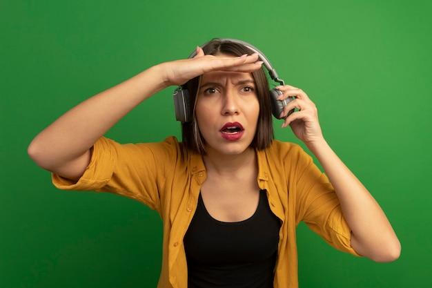 헤드폰에 충격을받은 예쁜 백인 여자가 녹색의 이마에 손바닥을 유지합니다.