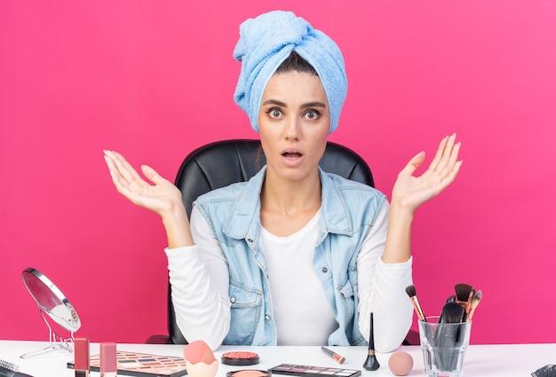 머리를 수건으로 감싼 채 테이블에 앉아 화장 도구를 들고 분홍색 벽에 격리된 복사 공간이 있는 충격을 받은 백인 여성