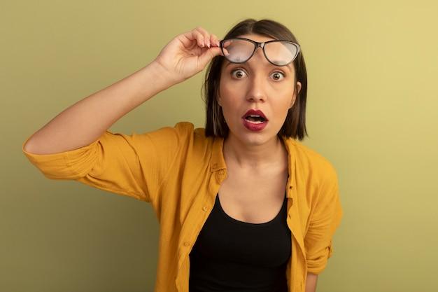 La donna graziosa scioccata tiene i vetri ottici e guarda la parte anteriore isolata sulla parete verde oliva