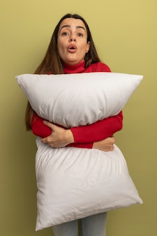 ショックを受けたきれいな女性は、オリーブグリーンの壁に分離された枕を保持します。