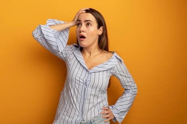 ショックを受けたきれいな女性は額に手を置き、オレンジ色の壁に隔離された側を見て