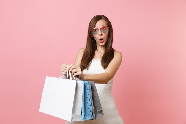 Shocked pretty woman in white dress and heart glasses holding multi colored packages bags with purchases after shopping
