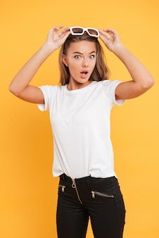 Shocked pretty young woman standing isolated
