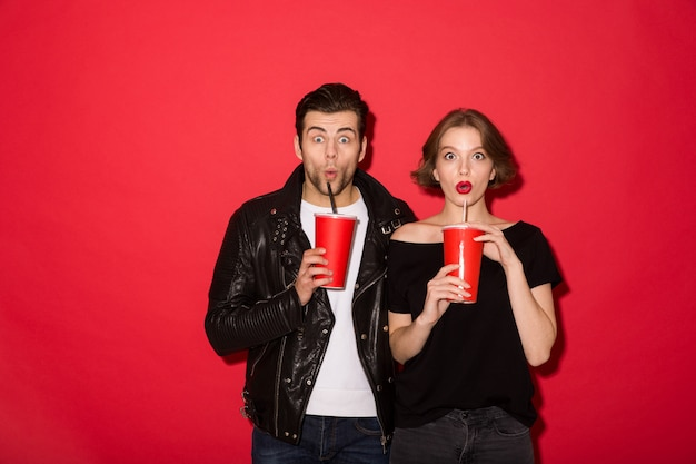 Shocked punk couple drinking soda and looking