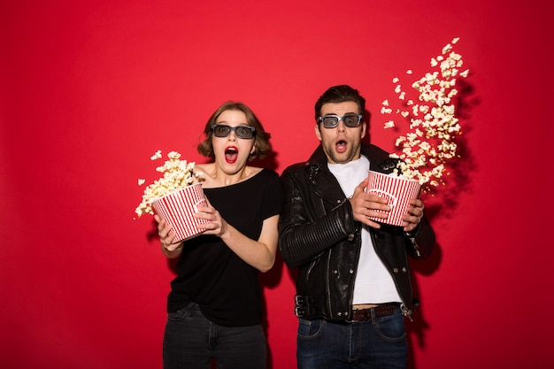 Shocked punk couple scatter popcorn and looking