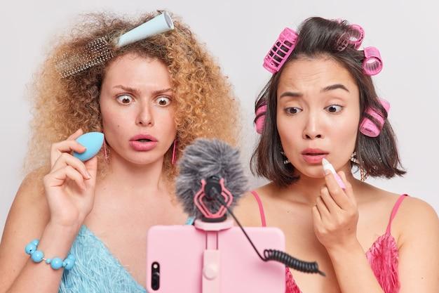 ショックを受けた困惑した女性モデルは、スマートフォンのカメラを注意深く見るスポンジで口紅とファンデーションを適用します