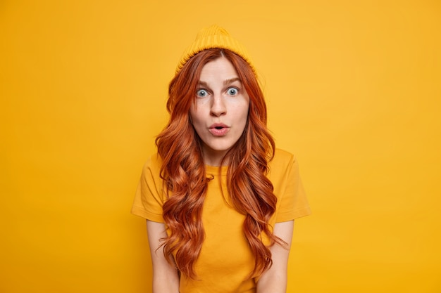 Shocked redhead girl stares speechless, has starled face expression opens mouth from amazement wears hat casual t shirt