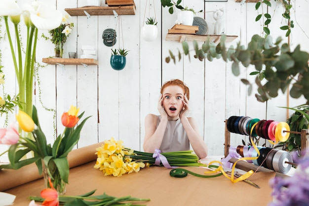 Shocked redhead lady while sitting in workshop