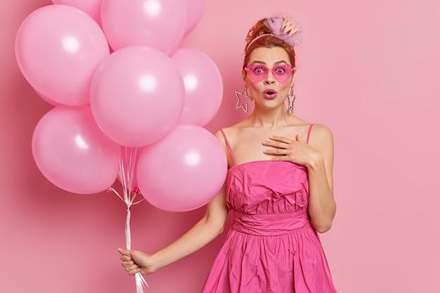 Потрясенная рыжая женщина смотрит, удивительно реагирует на поздравления от семьи, а коллеги празднуют день рождения, держит кучу надутых воздушных шаров, изолированных на розовой стене
