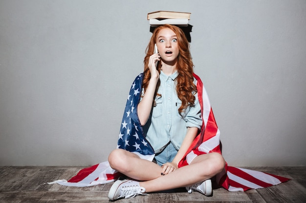 Shocked redhead young lady talking by phone.