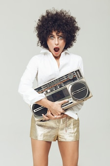 Shocked retro woman holding boombox.