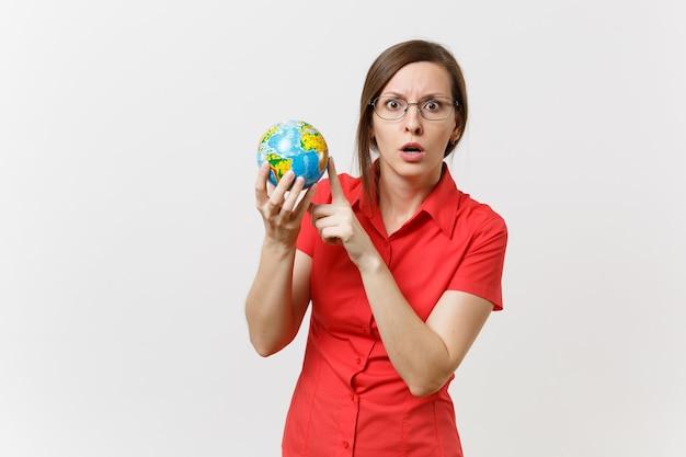 손바닥에 들고 빨간 셔츠에 충격된 슬픈 비즈니스 또는 교사 여자 흰색 배경에 고립 지구 글로브입니다. 환경 오염 문제. 자연 쓰레기, 환경 보호 개념을 중지합니다.