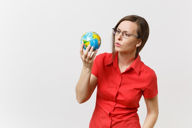 Shocked sad business or teacher woman in red shirt holding in palms earth globe isolated on white background. problem of environmental pollution. stop nature garbage, environment protection concept.