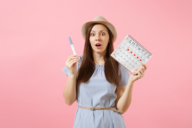 Shocked sad woman in blue dress, hat hold in hand pregnancy test, periods calendar for checking menstruation days isolated on pink background. medical, healthcare, gynecological concept. copy space.