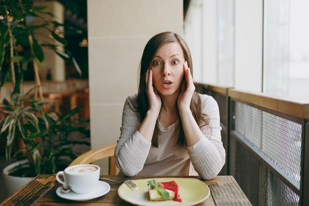 カプチーノ、ケーキ、自由時間のレストランでリラックスしてテーブルのコーヒーショップの大きな窓の近くに一人で座っているショックを受けた悲しい若い女性。カフェで休んでいる若い女性。ライフスタイルのコンセプト