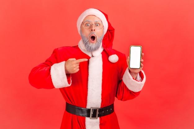 Шокированный санта-клаус, указывая на пустой дисплей смартфона, показывая удивленную рекламу.