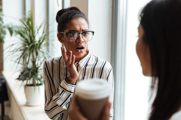 Shocked scared businesswomen colleagues talking