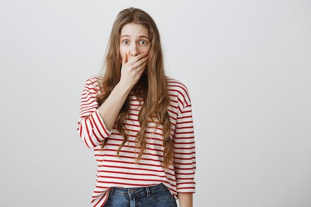 Шокированная испуганная девушка прикрывает рот испуганной и смотрит