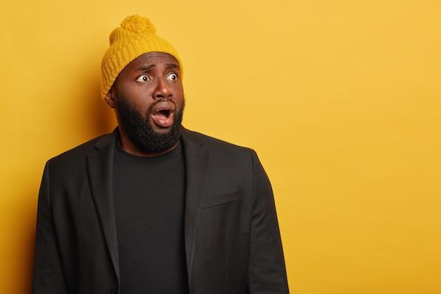 충격을받은 겁에 질린 남자가 오른쪽으로 돌아서 겁에 질린 표정으로 시선을 돌리고 입을 크게 벌리고 검은 양복과 노란 모자를 쓰고 흥분하고 놀라움을 느끼며 턱을 떨어 뜨립니다.
