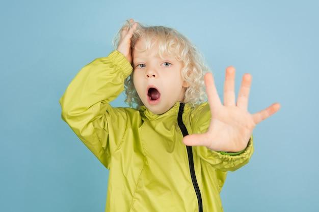 Шокирован, испуган. портрет красивого кавказского маленького мальчика изолированного на голубой стене. блондинка кудрявая мужская модель. концепция выражения лица, человеческие эмоции, детство, copyspace.