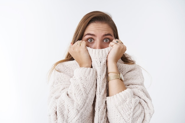Shocked scared stunned cute caucasian woman hiding face collar sweater pulling cloth nose widen eyes amazed speechless afraid watching horror standing stuned white background, frightened