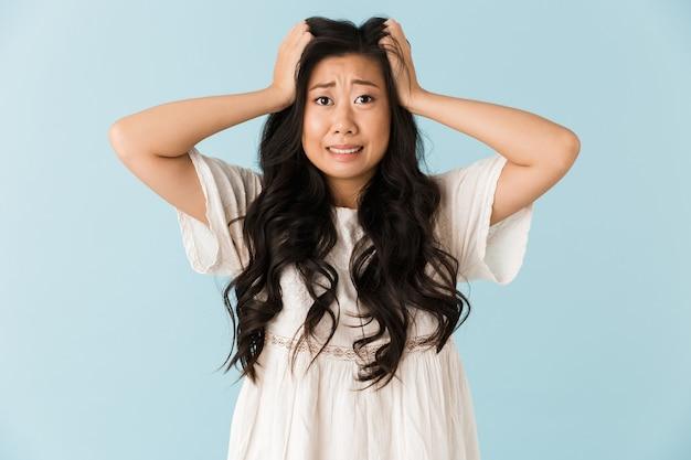 青い壁に孤立したポーズでショックを受けた怖い若いアジアの美しい女性