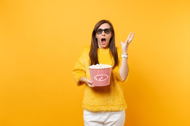 Shocked scared young girl in 3d imax glasses screaming, spreading hands, watching movie film holding popcorn isolated on bright yellow background. people sincere emotions in cinema, lifestyle concept.