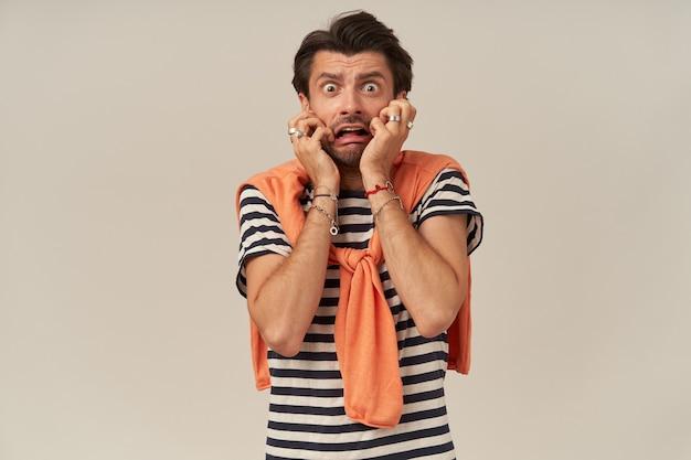 줄무늬 티셔츠와 스웨터에 수염이있는 충격을받은 겁 먹은 청년은 겁에 질려 겁에 질려 보입니다.