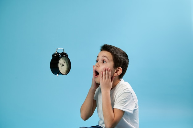 A shocked schoolboy looking with horror at a flying alarm clock and holding his face with his hands