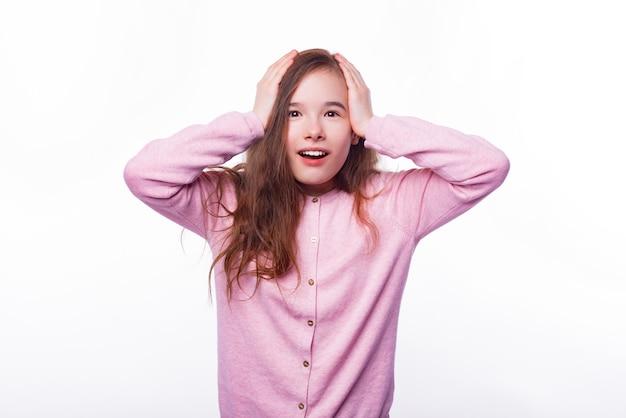 Shocked schoolgirl is holding her hands on head.