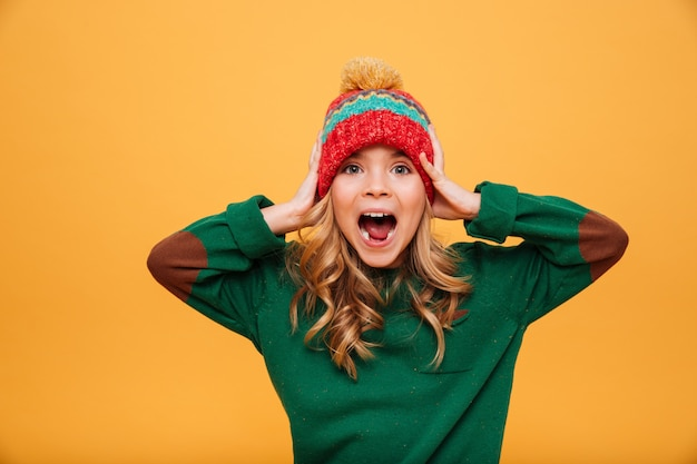 Shocked screaming young girl in sweater and hat holding her head while looking at the camera over orange
