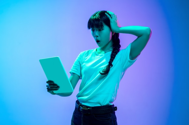 Shocked scrolling tablet young asian womans portrait on gradient bluepurple studio