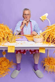 Shocked senior man work from home sits at white desk with folders paperclips bowl of cornflakes cut paper weras transparent glasses formal shirt tie around neck socks and slippers purple wall