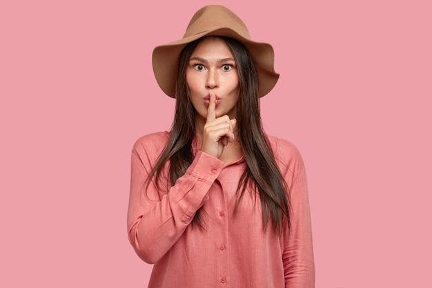 Una giovane donna castana lentigginosa seria scioccata chiede di mantenere il segreto al sicuro, dice zitto, chiede di mantenere il silenzio