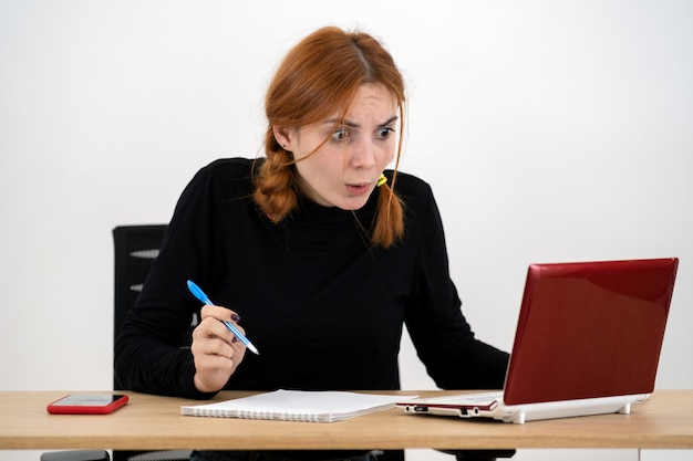 Shocked serious young office worker woman sitting behind working desk