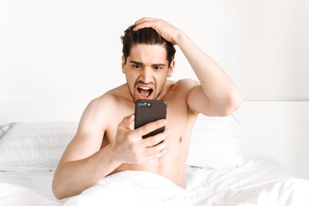 Шокирован мужчина без рубашки, глядя на мобильный телефон