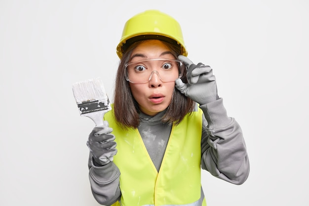 충격을 받은 숙련된 아시아 여성 디자이너는 흰색으로 격리된 안전모와 유니폼을 입고 집을 다시 꾸미는 그림 붓을 들고 있습니다.