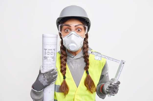 Shocked skilled female engineer holds blueprint and tape measure works on new construction project