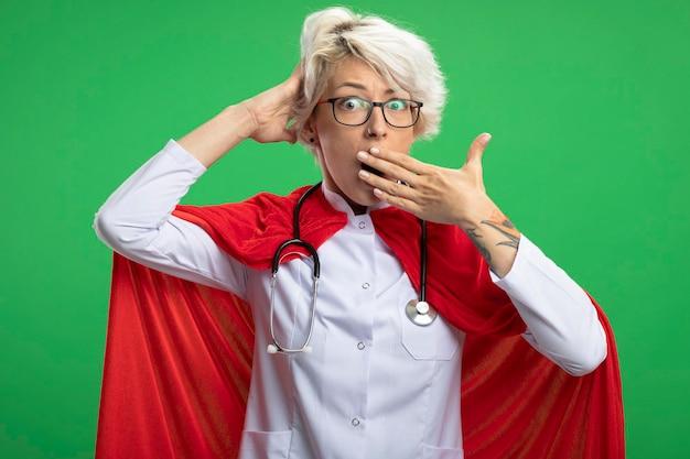 光学メガネの赤いマントと聴診器で医者の制服を着たショックを受けたスラブのスーパーヒーローの女性が置きます