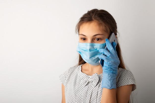 Шокированная маленькая девочка в медицинской маске и перчатках слышит плохие новости