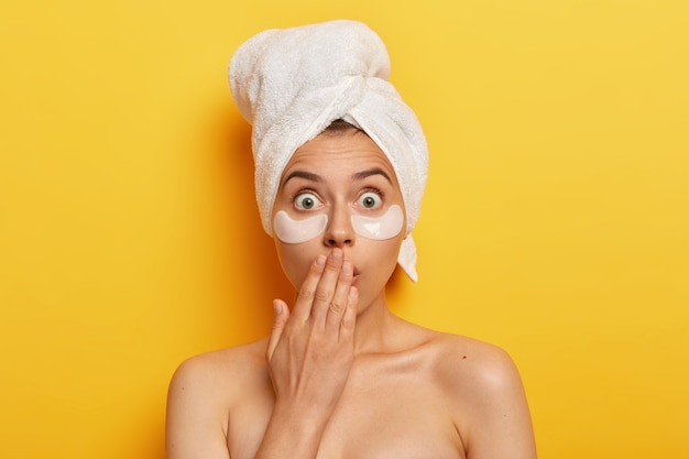 Shocked spa woman popping eyes, horrified by terrible relevation, nourishes undereye skin with beauty patches, wears wrapped towel on head, has anti wrinkle procedure, being naked.