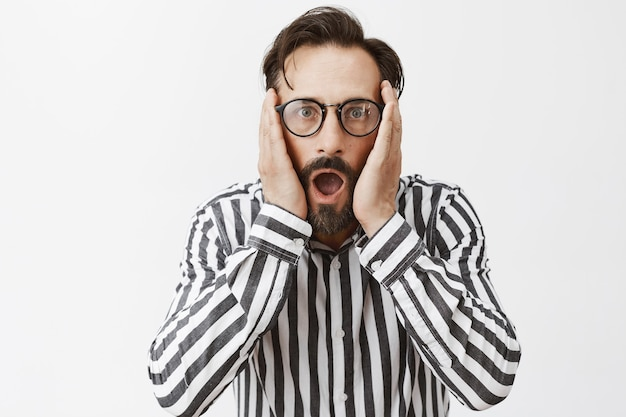 Shocked and speechless bearded mature man posing