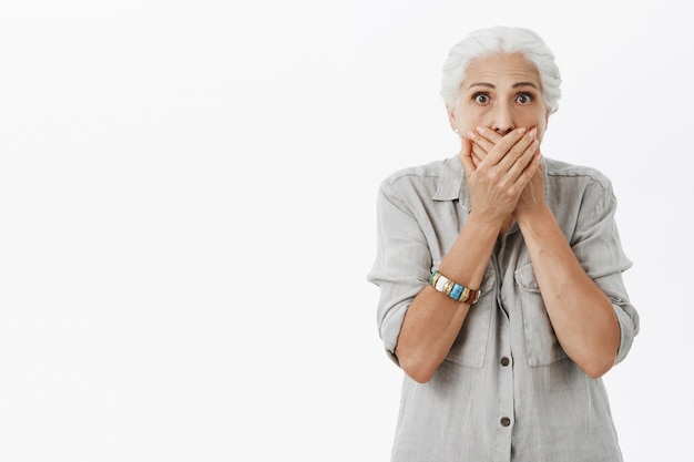 Shocked speechless granny shut mouth with hands and stare