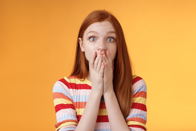 Shocked speechless impressed sensitive redhead european girl reacting stunning rumor gossiping find out secret gasping cover mouth palm stare camera astonished surprised, orange background.