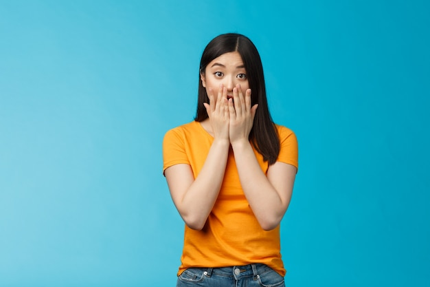 Шокированная безмолвная ошеломленная азиатская девушка смотрит в камеру прикрывает рот ладонями, поднимает брови, задыхается от удивления, сожалеет, слыша плохие новости, стоит на удивленном синем фоне, носит желтую футболку.