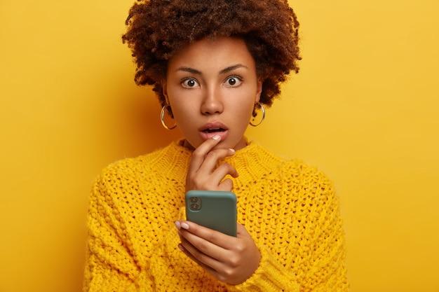 La giovane donna afro senza parole ha trovato la foto sulla pagina web sociale, sussulta per la meraviglia, tiene in mano uno smartphone moderno, tiene la bocca spalancata, indossa un maglione lavorato a maglia brillante, orecchini, controlla la casella di posta elettronica