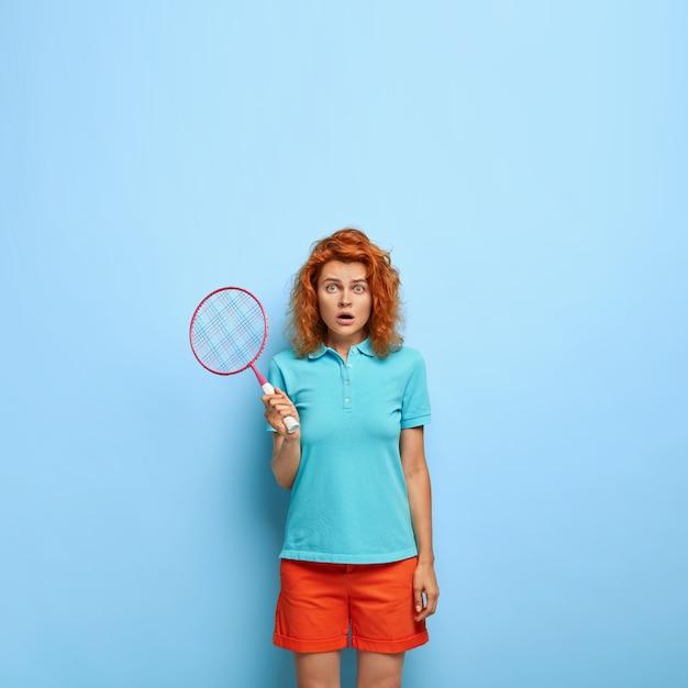 Il tennista sportivo scioccato tiene la racchetta e guarda con espressione indignata