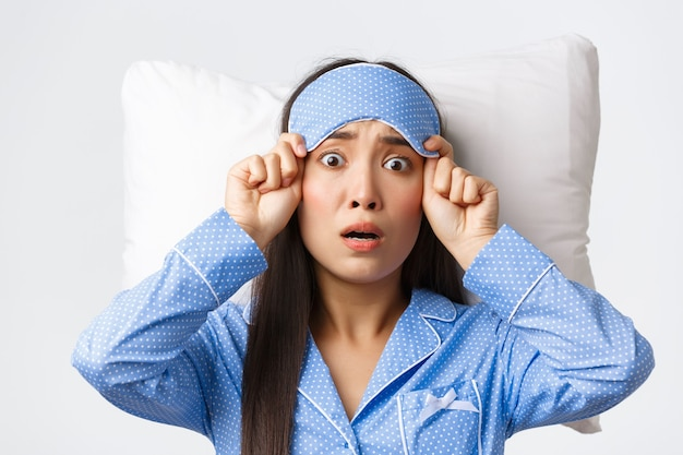 Shocked and startled anxious asian woman in blue pajamas, lying in bed on pillow