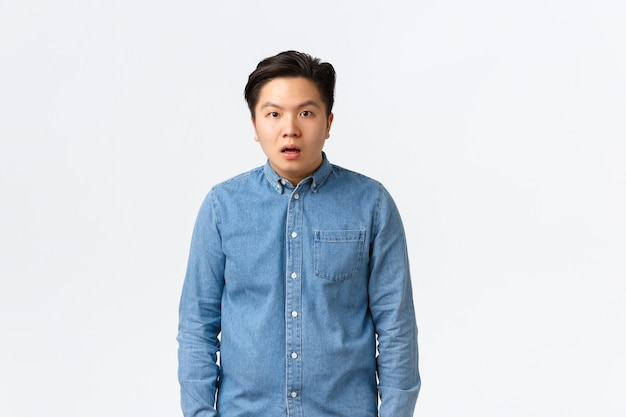 Shocked and startled asian male student, drop jaw and stare dumb at camera, cant understand what happening, feeling confused and puzzled, looking speehless over white background.