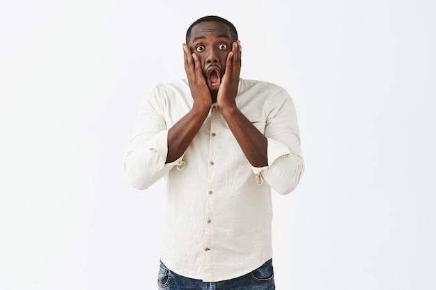Ragazzo giovane scioccato e sorpreso in posa contro il muro bianco
